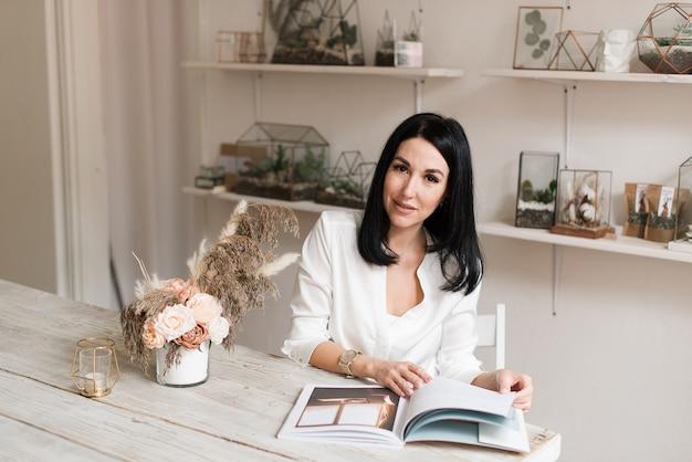 Stijlvolle mooie brunette in een wit overhemd en met een klok aan het lezen van een tijdschrift aan tafel