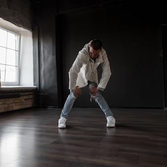 Stijlvolle mooie hiphop danseres in modieuze kleding met blauwe gescheurde spijkerbroek met sneakers dansen in een donkere dansstudio