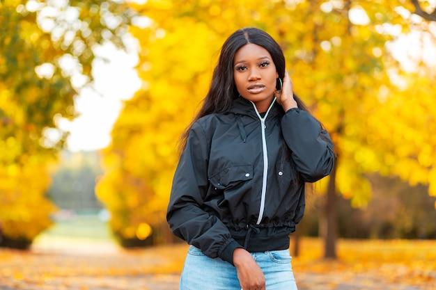 Stijlvolle mooie jonge afro-amerikaanse vrouw in een modieus jasje met spijkerbroek loopt in een park tegen een achtergrond van geel herfstgebladerte