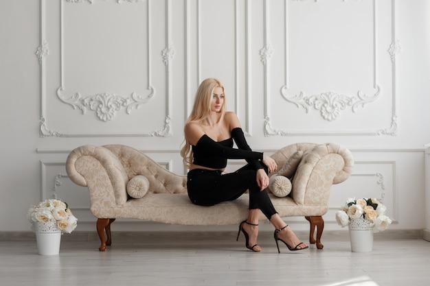 Stijlvolle mooie jonge blonde vrouw in zwarte mode kleding, zittend op de bank in de vintage studio
