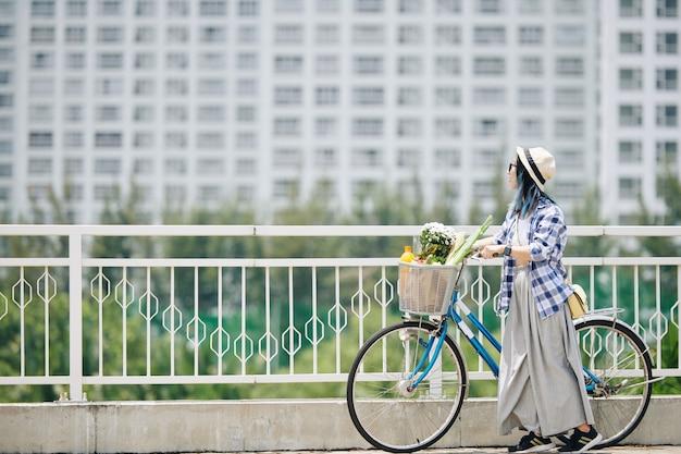Stijlvolle mooie jonge chinese vrouw in geruite overhemd en wijde broek staande op de brug naast haar fiets en genietend van het uitzicht