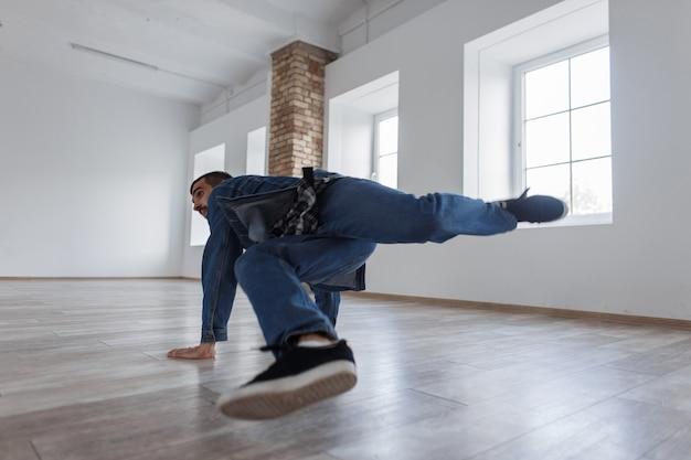 Stijlvolle mooie jonge danseres in jeans jasje en spijkerbroek dansen in een dansstudio