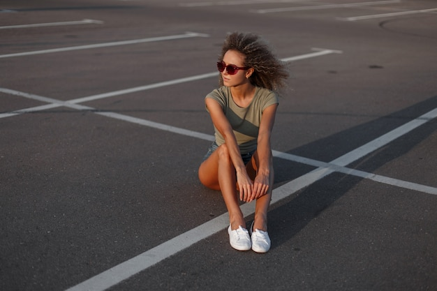 Stijlvolle mooie jonge hipster model vrouw met krullend kapsel in zonbeschermende bril in denim shorts met een stijlvol t-shirt en witte sneakers zittend op het asfalt op straat