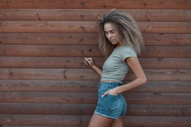 Stijlvolle mooie jonge krullende hipster trendy vrouw in mode denim kleding in de buurt van een houten muur