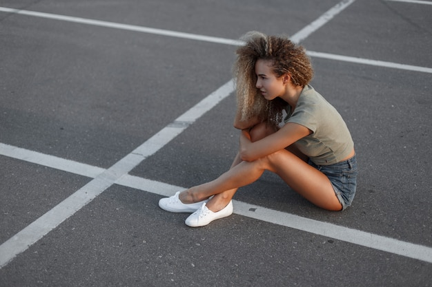 Stijlvolle mooie jonge krullende vrouw in mode denim shorts en witte sneakers zit op het asfalt