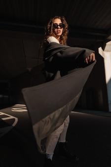 Stijlvolle mooie jonge krullende vrouw model met zonnebril in een modieuze jas loopt in de stad in zonlicht en schaduwen. vrouwelijke stedelijke elegante stijl