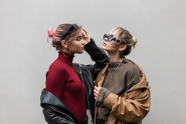 Stijlvolle mooie jonge tieners vriendin in modieuze kleding met bril, lederen wendingen en trui staan en poseren in de buurt van grijze muur in de stad