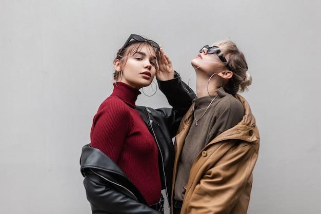 Stijlvolle mooie jonge vriendinnen vrouw in een modieuze leren jas en gebreide trui met zonnebril staan op een grijze achtergrond in de stad