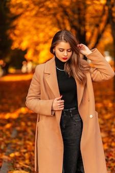 Stijlvolle mooie jonge vrouw in een beige jas en trui loopt in een herfstpark met gekleurd herfstgebladerte