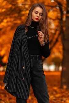 Stijlvolle mooie jonge vrouw in een modieus zwart pak met een blazer en een trui in een herfstpark buitenshuis. elegante vrouwelijke stijl en mode