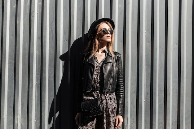 Stijlvolle mooie jonge vrouw in een modieuze zwarte leren jas met een jurk en een handtas in een zonnebril in de buurt van een metalen muur op straat