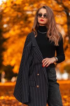 Stijlvolle mooie jonge vrouw in modieuze kleding met een jas, trui en zonnebril poseert in een park met fel herfstgekleurd gebladerte. vrouwelijke zakelijke stijl en schoonheid