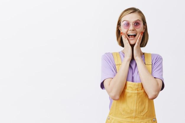 Stijlvolle mooie jonge vrouw in zonnebril en zomerkleding die er zorgeloos uitziet, de handen vastpakt en er opgewonden uitziet, zich verheugt met geweldig nieuws