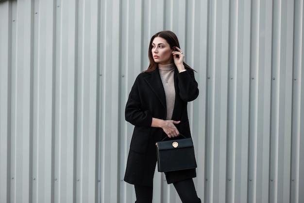 Stijlvolle mooie jonge vrouw met bruin haar in zwarte modieuze jas met stijlvolle lederen zwarte handtas staat in de buurt van zilveren metalen vintage muur. moderne luxe meisje mannequin buitenshuis.sensuele dame