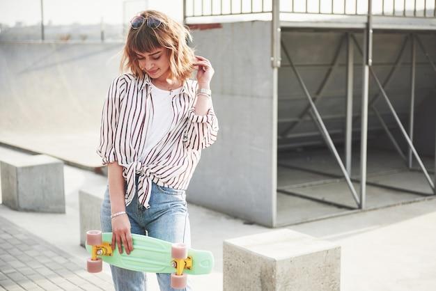 Stijlvolle mooie jonge vrouw met een skateboard, op een mooie zonnige zomerdag.