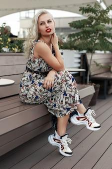 Stijlvolle mooie jonge vrouw met rode lippen in een modieuze jurk met fashion sneakers zitten en ontspannen op een houten bankje in de straat