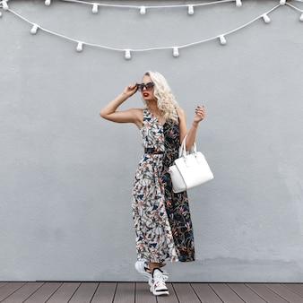 Stijlvolle mooie jonge vrouw met zonnebril in een modieuze jurk in de buurt van een grijze muur