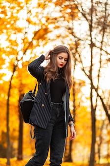 Stijlvolle mooie jonge vrouw model in een zwart pak met een modieuze blazer, trui en rugzak wandelingen in een herfstpark met geel herfstgebladerte bij zonsondergang
