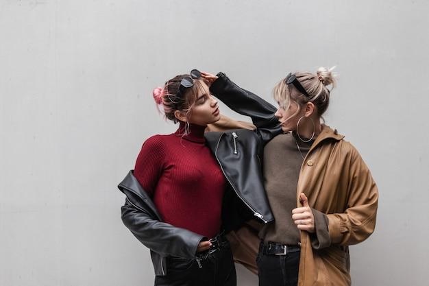 Stijlvolle mooie jonge vrouwen model vriendinnen met modieuze vintage oversized jas en gebreide trui poseren in de buurt van grijze muur