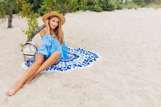 Stijlvolle mooie lachende vrouw zittend op zand met magere benen op zomervakantie op tropisch strand met strooien hoed, zilveren rugzak