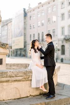 Stijlvolle mooie paar aziaten pasgetrouwden lopen op de straten van het oude stadscentrum op een zonnige dag van hun bruiloft.