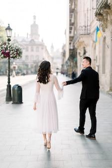 Stijlvolle mooie paar aziaten pasgetrouwden lopen op de straten van venetië op een zonnige dag van hun bruiloft