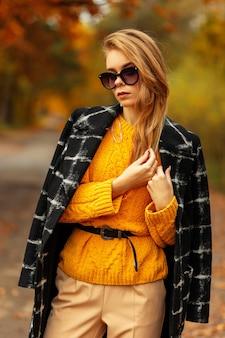 Stijlvolle mooie scandinavische vrouw met mode-zonnebril in een vintage gele trui met een zwarte jas loopt in het park met oranje herfstbladeren