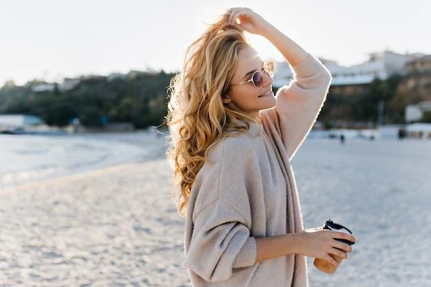 Stijlvolle mooie vrouw blinde in beige oversized trui en bruine zonnebril loopt aling strand met kartonnen kopje thee.