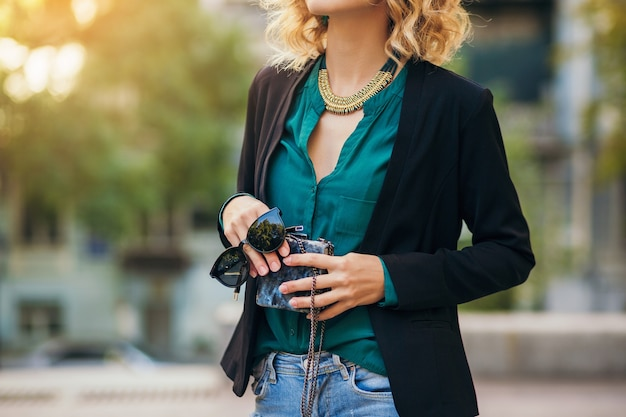 Stijlvolle mooie vrouw in spijkerbroek en jas lopen in straat met kleine portemonnee, elegante stijl, lente modetrends