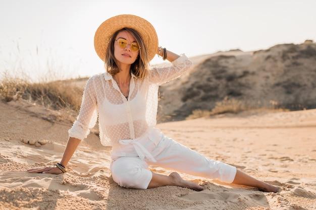 Stijlvolle mooie vrouw in woestijnzand in witte outfit stro hoed dragen op zonsondergang