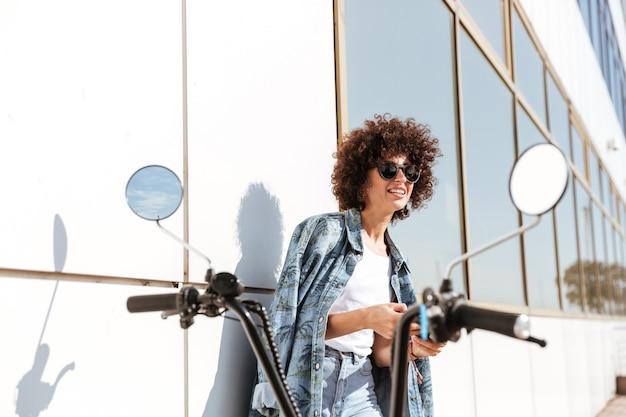 Stijlvolle mooie vrouw in zonnebril met behulp van mobiele telefoon