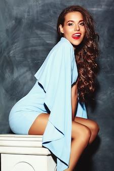 Stijlvolle mooie vrouw model met rode lippen in zomer heldere kleurrijke hipster blauwe jurk