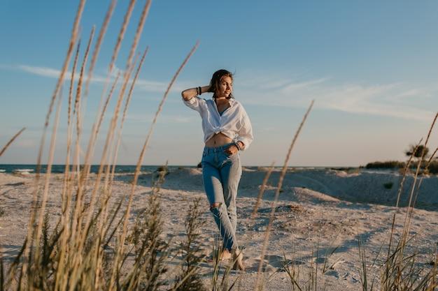 Stijlvolle mooie vrouw op zomervakantie op het strand, bohemien stijl, jeans