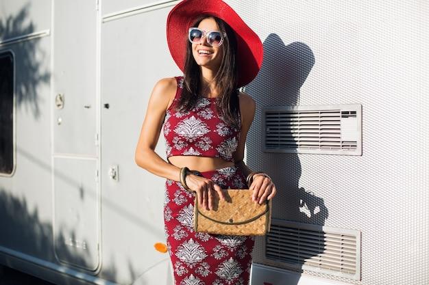 Stijlvolle mooie vrouw poseren tegen zilveren aanhangwagen in tropische stijl outfit
