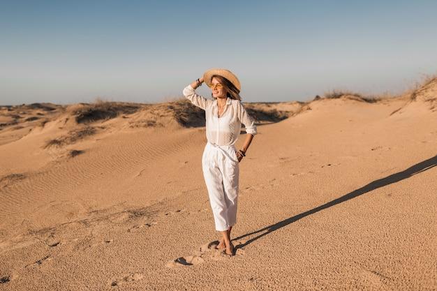 Stijlvolle mooie vrouw wandelen in woestijnzand in witte outfit stro hoed dragen op zonsondergang