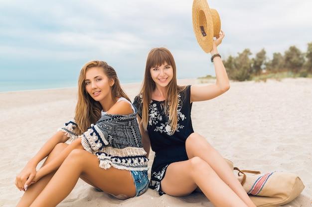 Stijlvolle mooie vrouwen op zomervakantie op het strand, bohemien stijl, vrienden samen, modetrend, accessoires, glimlachen, blije emotie, positieve stemming, emotionele gezichtsuitdrukking, verrast, blij