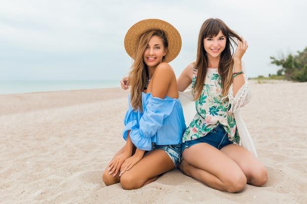 Stijlvolle mooie vrouwen op zomervakantie op tropisch strand, bohemien stijl, vrienden reizen samen, modetrend, accessoires, glimlachen, vrolijke emotie, positieve stemming, strooien hoed, zittend op zand