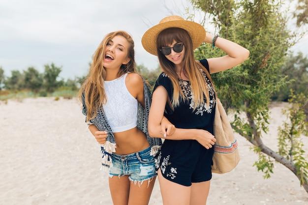 Stijlvolle mooie vrouwen op zomervakantie op tropisch strand, bohemien stijl, vrienden samen, mode-accessoires, glimlachen, gelukkige emotie, positieve stemming, korte broek, strooien hoed, plezier hebben