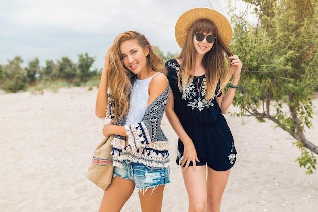 Stijlvolle mooie vrouwen op zomervakantie op tropisch strand, bohemien stijl, vrienden samen, mode-accessoires, glimlachen, vrolijke emotie, positieve stemming, korte broek, strooien hoed, plezier maken