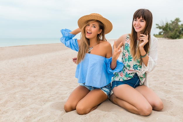 Stijlvolle mooie vrouwen zittend op zand op zomervakantie op tropisch strand, bohemien stijl, vrienden reizen samen, modetrend accessoires, lachende gelukkige emotie, positieve stemming, strooien hoed