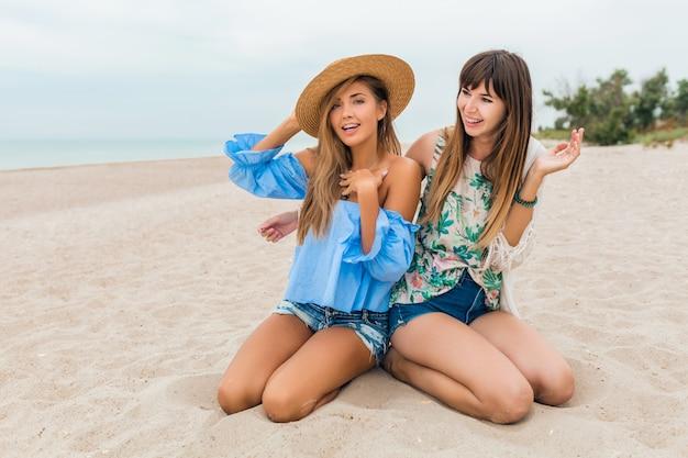 Stijlvolle mooie vrouwen zittend op zand op zomervakantie op tropisch strand, strooien hoed