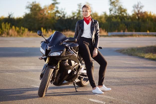 Stijlvolle motorrijder draagt modieuze motorkleding, witte sportschoenen, poseert bij haar motor, heeft rust na lange reis