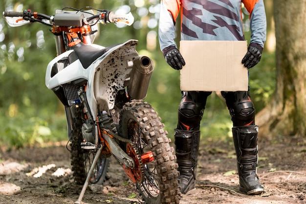 Stijlvolle motorrijder met kartonnen bord