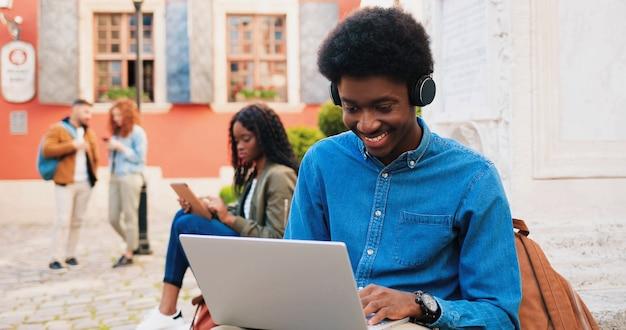 Stijlvolle multiraciale student die zijn laptopcomputer gebruikt, terwijl hij geniet op straat. portret van tiener afro-amerikaanse man buiten in de zomer. stedelijke achtergrond. jeugd concept