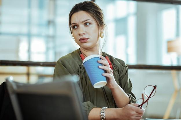 Stijlvolle oorbellen. zwangere zakenvrouw draagt stijlvolle oorbellen met kopje koffie