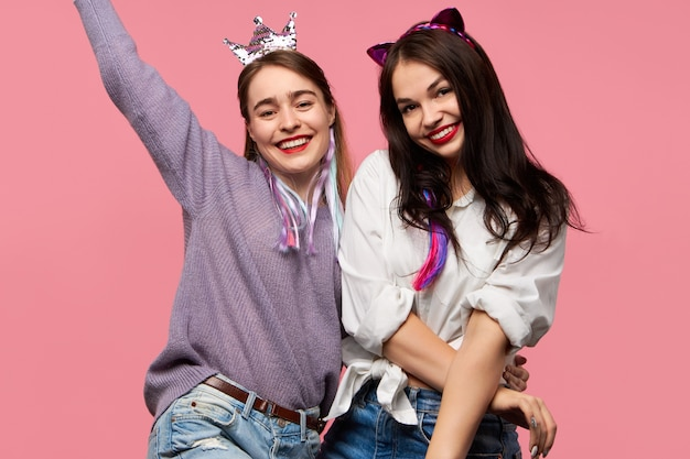 Stijlvolle opgewonden jonge vriendinnen dragen lichte make-up, nep dierenoren en kroon met plezier op feestje, dansen, blij om elkaar te zien, geïsoleerd poseren