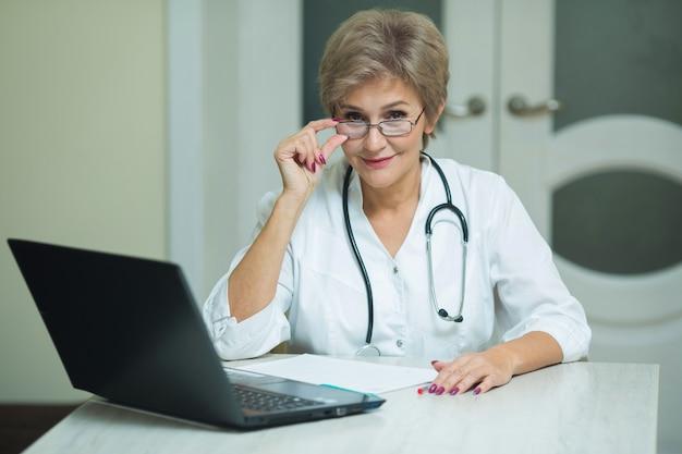 Stijlvolle oude vrouw in een witte jas zittend aan de tafel in het ziekenhuis met een laptop