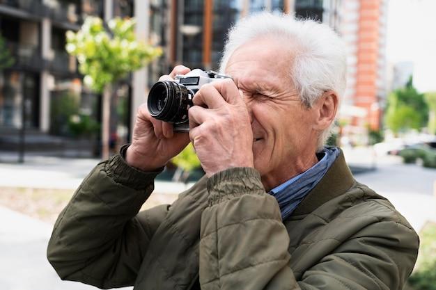 Stijlvolle oudere man in de stad die camera gebruikt om foto's te maken
