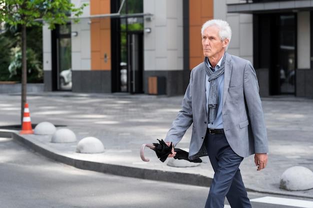 Stijlvolle oudere man in de stad die de straat oversteekt terwijl hij een paraplu vasthoudt