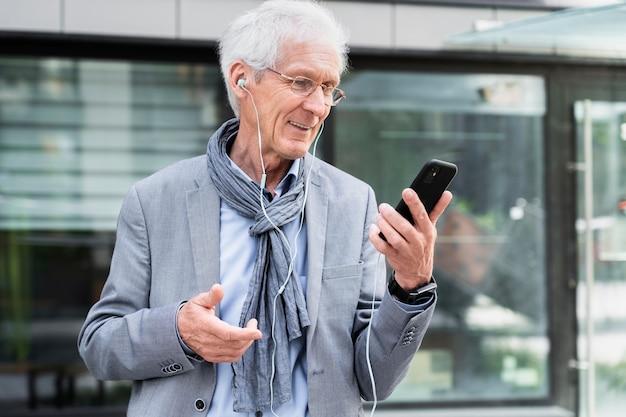 Stijlvolle oudere man in de stad die smartphone en oortelefoons gebruikt voor videogesprekken